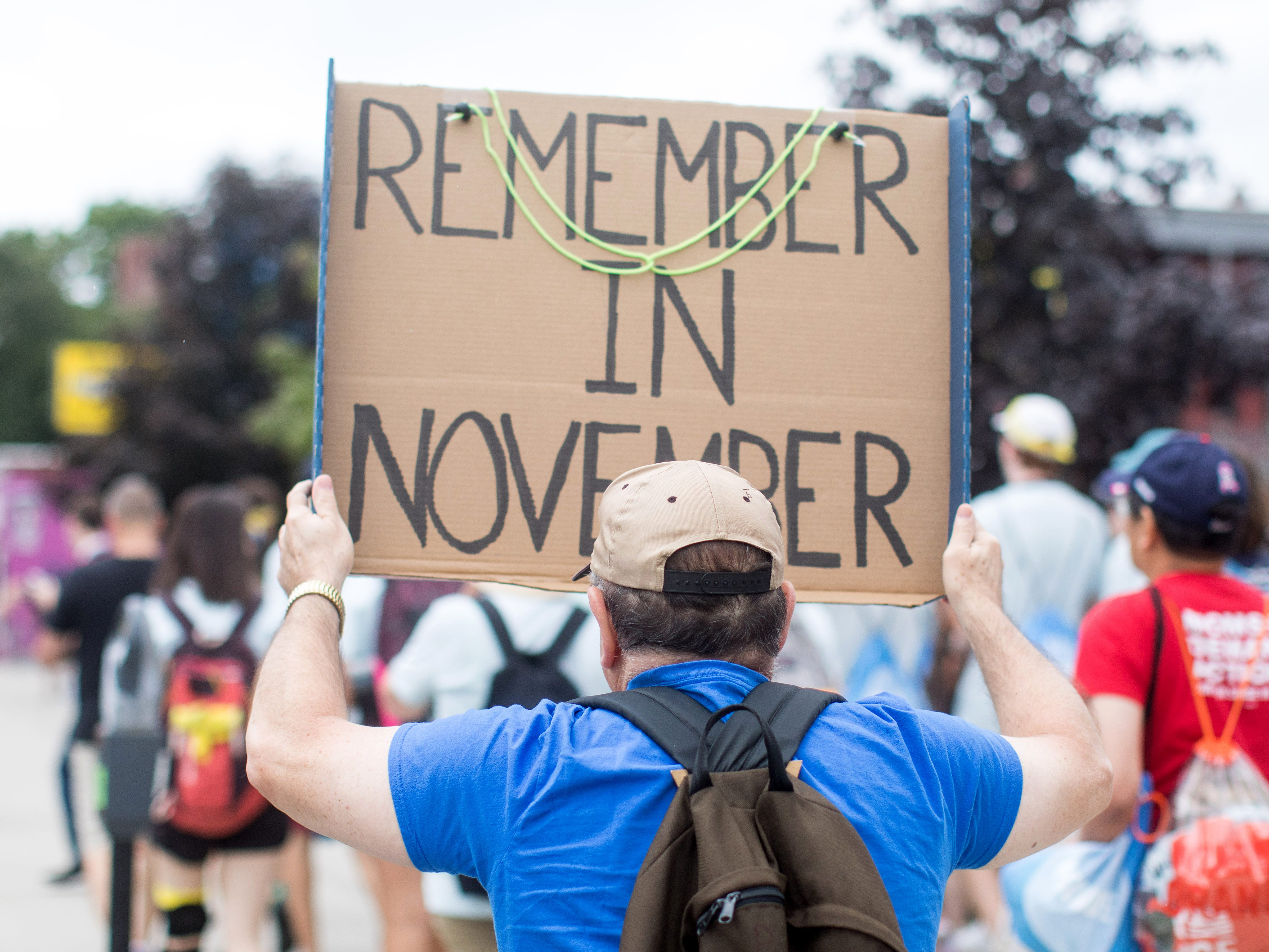 """An activist holds a sign that reads """"Remember in November"""" during the 50 Miles More walk against gun violence which will end with a protest at the Smith and Wesson Firearms factory on Aug. 23, 2018 in Worcester, Mass."""