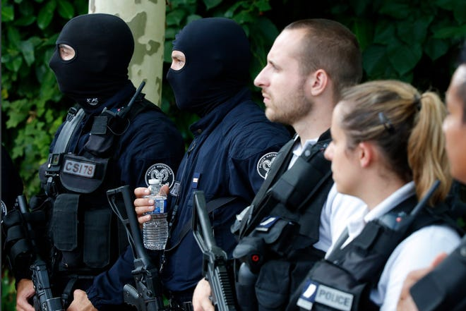 French police officers guard the area after a knife attack Thursday, Aug. 23, 2018 in Trappes, west of Paris. A man flagged by French authorities as a suspected radical killed his mother and sister and seriously injured another woman in a knife attack Thursday that was quickly claimed by the Islamic State group.
