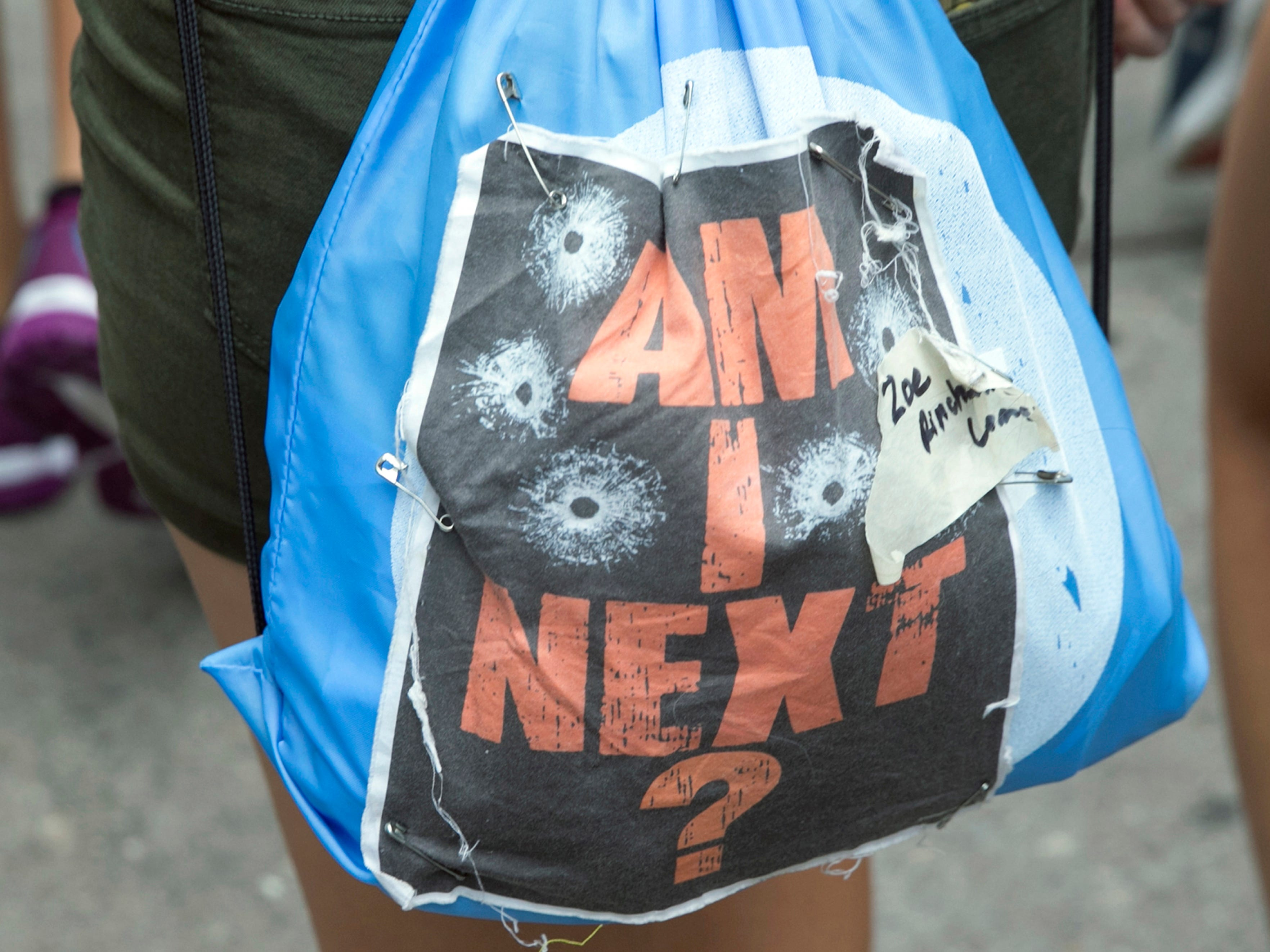 A youth wears a backpack with a sign that reads 'Am I Next?' during a youth march to protest gun violence, in Worcester, Mass. on Aug. 22, 2018.
