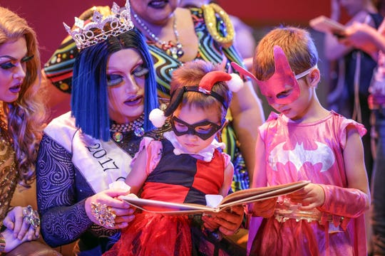 Indianapolis: Ida Kay, center left, reads a story to Harley Quinn dressed as Harley Quinn and Alexandria Burns dressed as Bat Girl during Drag Queen Story Time on July 22, 2017,  at the Central Library.