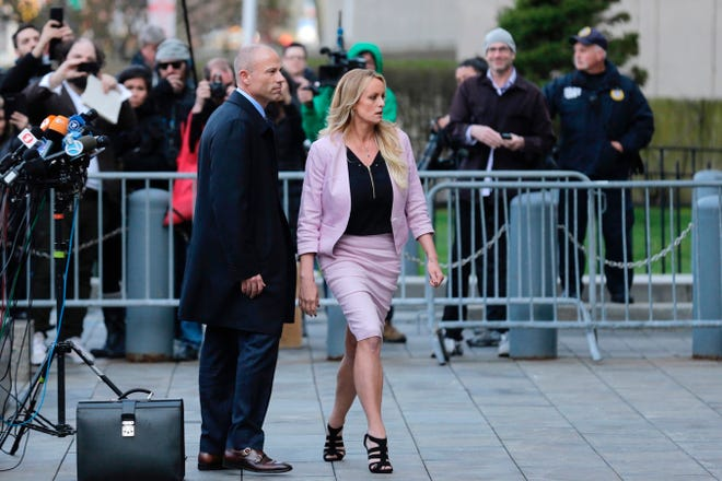Porn actress Stormy Daniels, accompanied by her attorney, Michael Avenatti, left, leaves federal court, Monday, April 16, 2018 in New York. A U.S. judge listened to more arguments about President Donald Trump's extraordinary request that he be allowed to review records seized from his lawyer, Michael Cohen, office as part of a criminal investigation before they are examined by prosecutors. The raid carried out last Monday at Cohen's apartment, hotel room, office and safety deposit box sought bank records, records on Cohen's dealing in the taxi industry, Cohen's communications with the Trump campaign and information on payments made in 2016 to former Playboy model Karen McDougal and to Daniels. (AP Photo/Seth Wenig) ORG XMIT: NYSW307