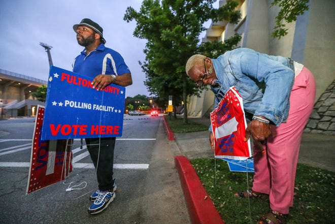 Poll workers Chris Nolan, left, and Raphallia Edwards prepare signage at Henry W. Grady High School in Atlanta on Tuesday May 22, 2018.