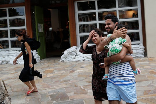 People shield themselves from the wind in front of a store with stacked sandbags in preparation for Hurricane Lane, Thursday, Aug. 23, 2018, in Honolulu, Hawaii. (AP Photo/John Locher) ORG XMIT: HIJL107