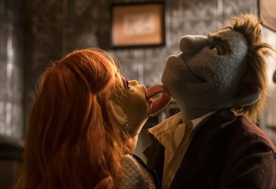 "Things get hot in the office between Sandra and Phil in ""The Happytime Murders."""