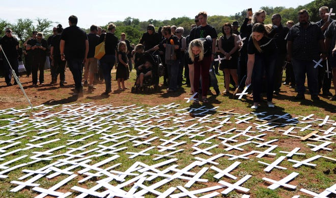 """In this photo taken Oct. 30, 2017 people place white crosses, representing farmers killed in the country, at a ceremony at the Vorrtrekker Monument in Pretoria, South Africa.  U.S. President Donald Trump has tweeted that he has asked the Secretary of State Mike Pompeo to """"closely study the South African land and farm seizures and expropriations and the large scale killing of farmers."""" Trump added, """"South African Government is now seizing land from white farmers."""" (AP Photo) ORG XMIT: XDF104"""