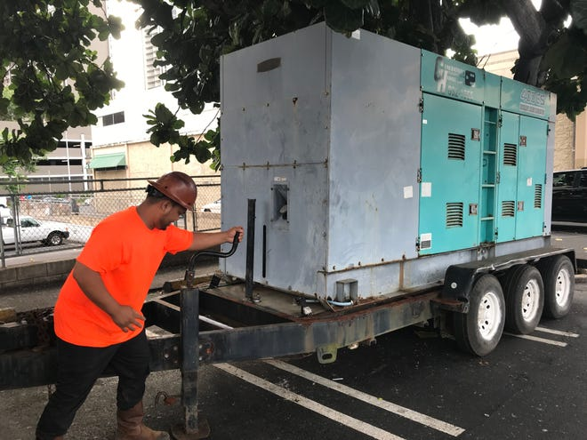 Justin Pagba installed a generator in the parking lot of a Longs Drugs in Honolulu in case Hurricane Lane knocks out power to the state capitol.