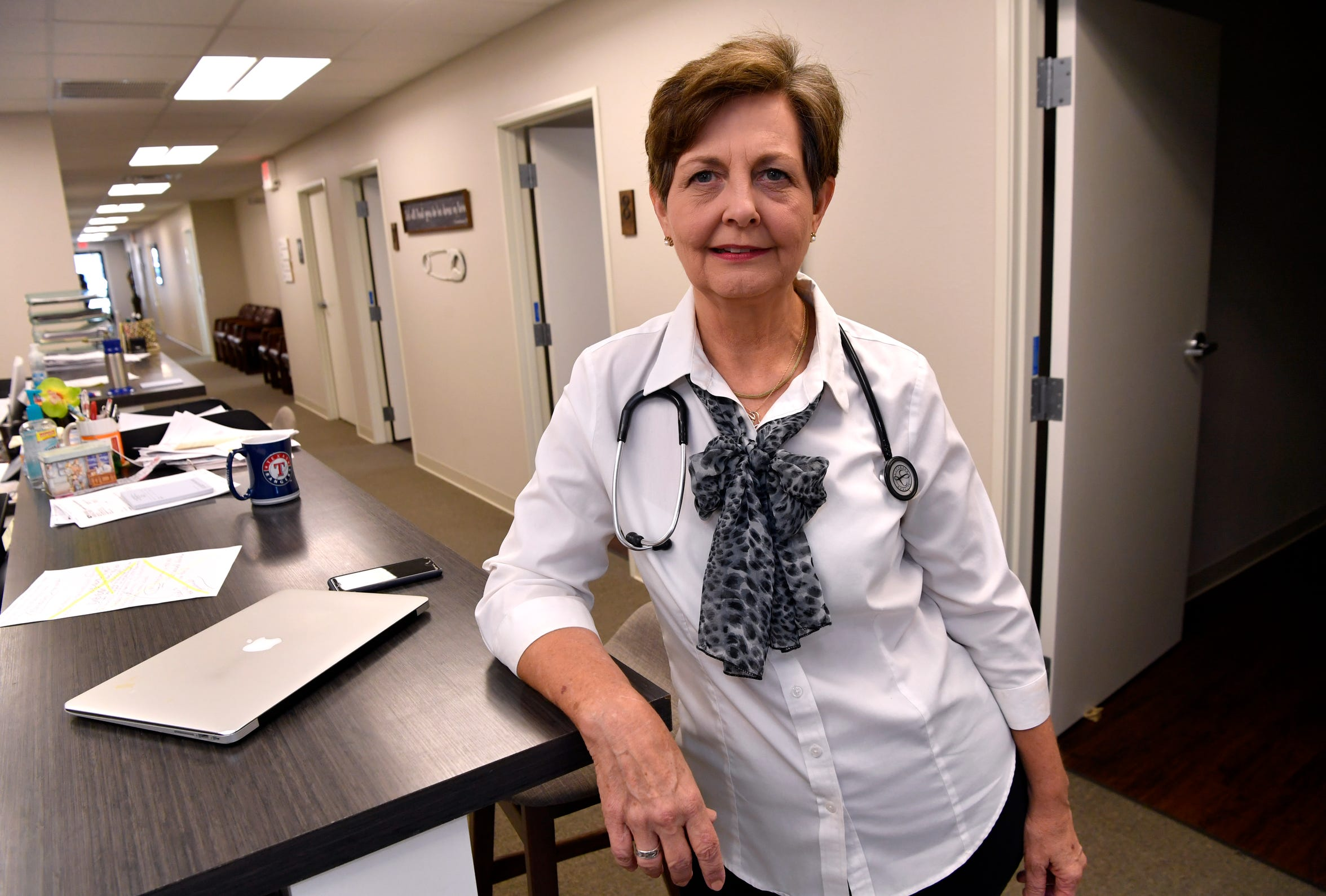 """It's about the people, it's taking care of families,"" said Dr. Rae Ann Hamilton, here standing at a nurse's station at Abilene Family Practice on Aug. 23. After 34 years, Hamilton retired."
