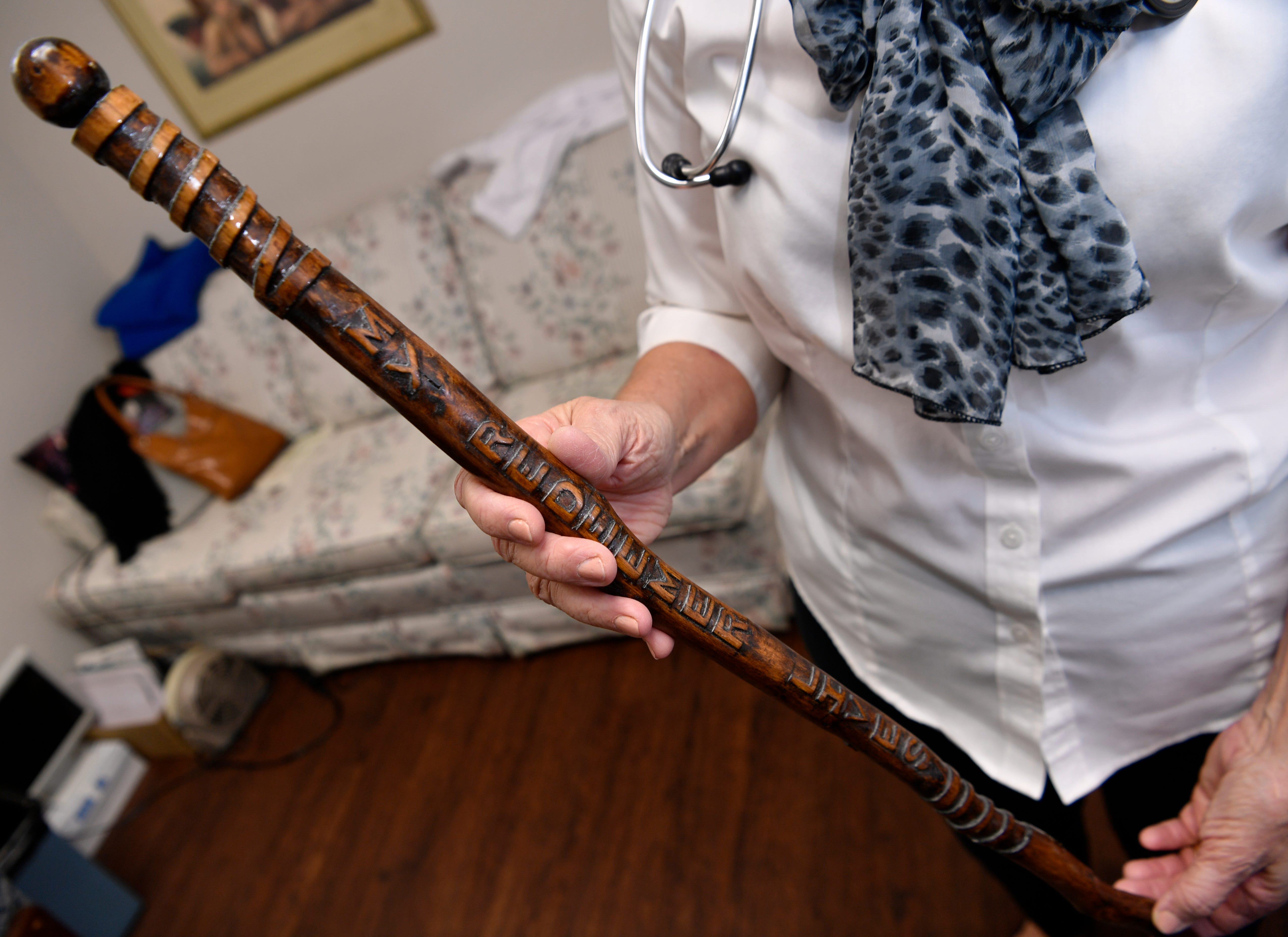 Dr. Rae Ann Hamilton holds the walking stick a patient gave her. It is carved with Christian references.
