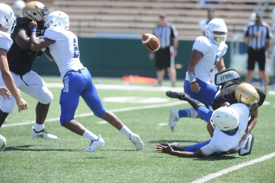 An Abilene Eagles defender forces a Copperas Cove fumble during Abilene High's scrimmage on Friday.