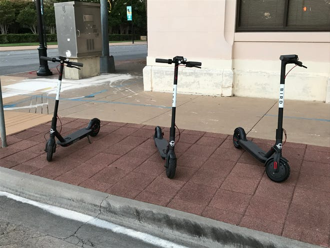 Bird electric scooters parked in downtown Abilene in August.
