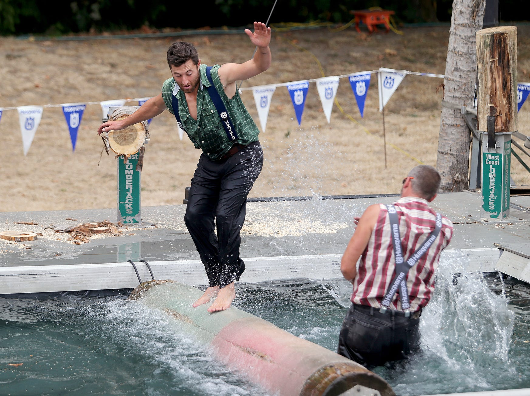 Scott Thompson dunks Darren Dean in the log roll in the West Coast Lumberjack Show at the Kitsap County Fair & Stampede on Friday, August 24, 2018 at the Kitsap County Fairgrounds.