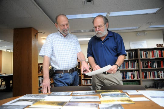 Joe Standaert, left, and Ron Vinson look over material that will be featured in an exhibit about Montreat photographer Alice Margaret Dickinson that opens at the Presbyterian Heritage Center on Sept. 1.