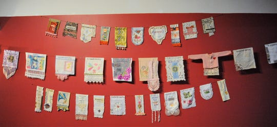 Many of prayer flags made by Jean Tomaso Moore can be found along a wall in the narthex of St. James Episcopal Church in Black Mountain, while most are hanging overhead.