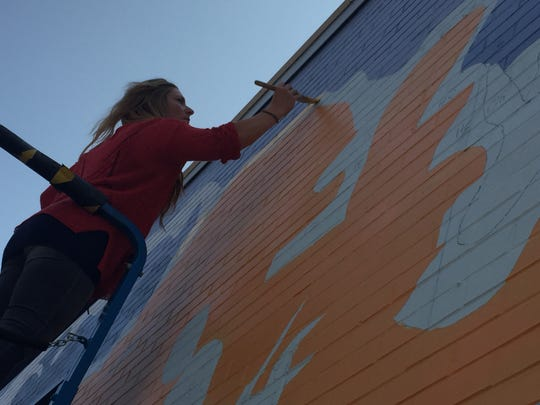 Jess Graham of Morrisville paints her mural on Cherry Street in Burlington on Friday, Aug. 24, 2018.