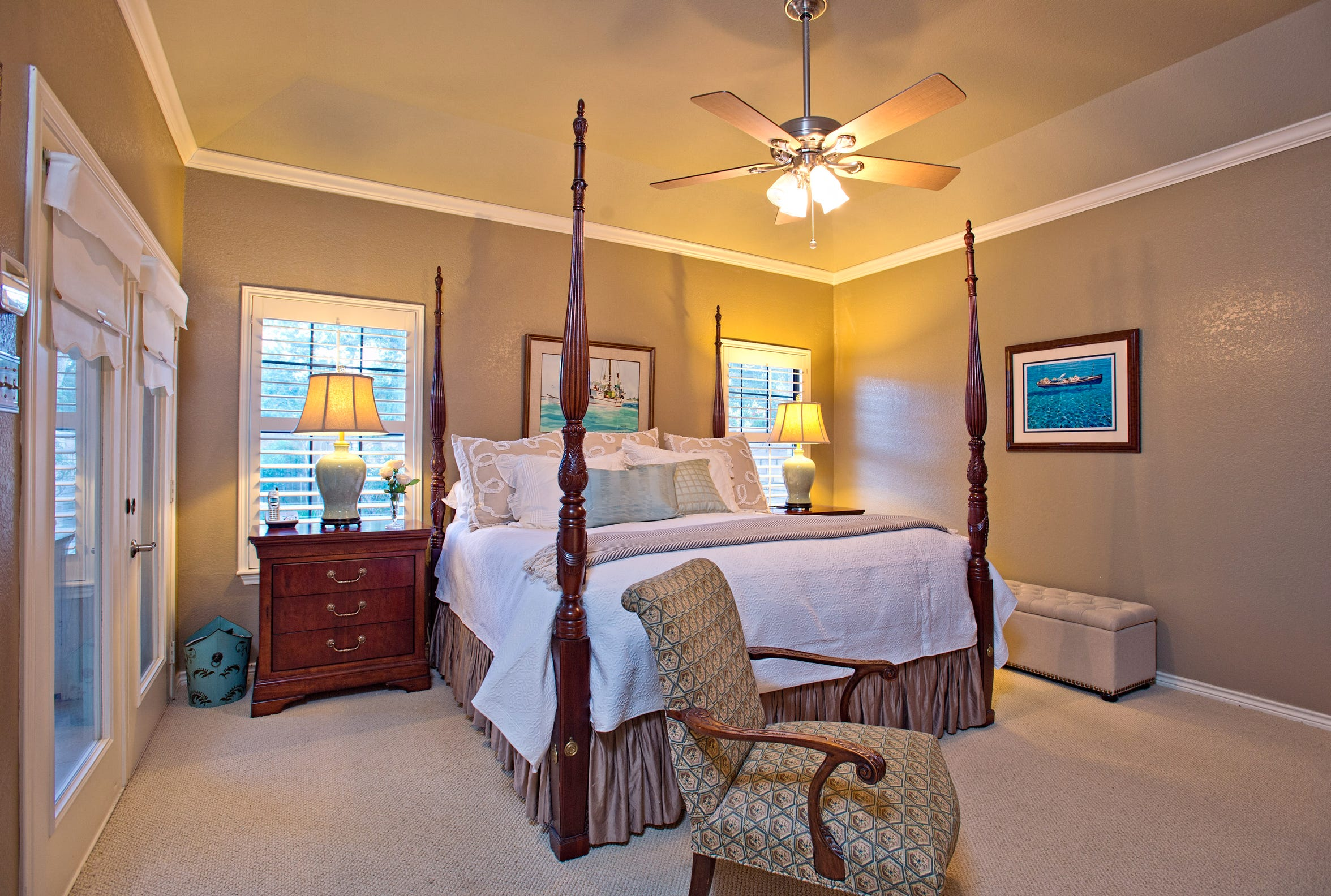 The master bedroom opens to the sun room and features plantation shuttered windows bringing in wonderful natural light in to the room
