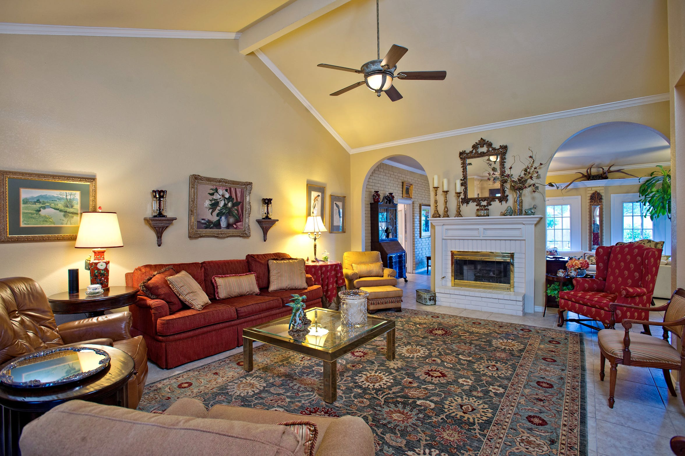 The spacious living area features an attractive fireplace set between two archways, a cathedral ceiling and a columned entry.