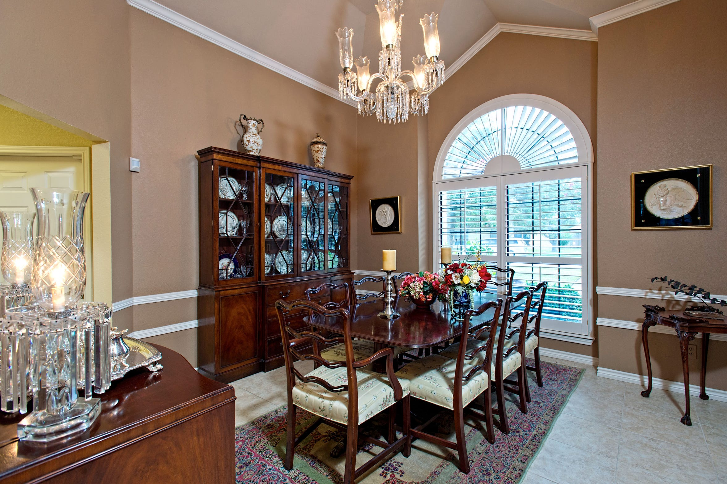 Dine in style in the formal dining room, open to the entry and living space; the area features a cathedral ceiling, crown molding and a beautiful plantation shuttered arched window.