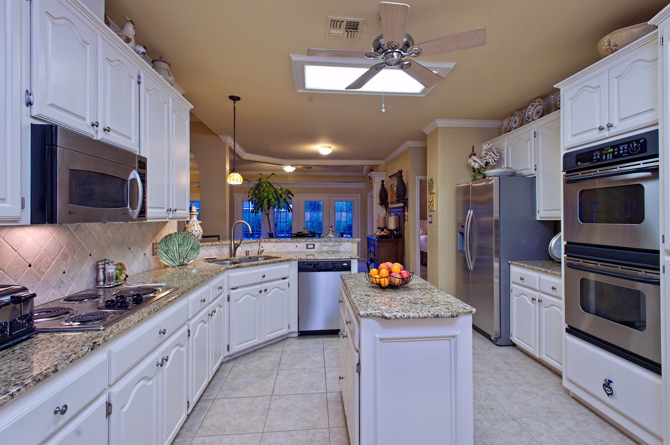 The spacious kitchen boasts granite counters and island and stainless steel appliances.