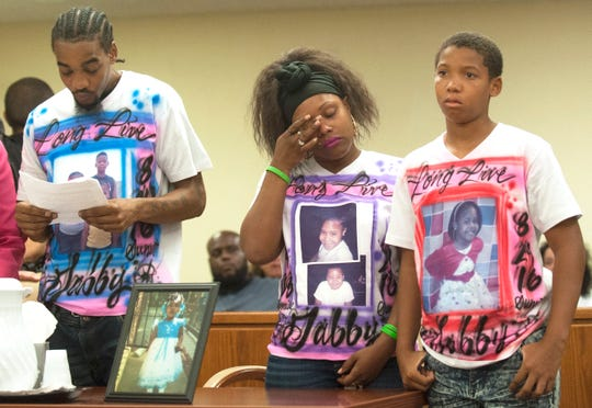 Meresa Carter, mother of Gabby Hill-Carter, center, wipes away tears as she stands with her husband Will Phillips, left, and step-son Kasir Phillips, right, as Will Phillips reads a statement during the sentencing of Tyhan Brown, who was convicted of fatally shooting 8-year-old Gabby Hill-Carter as she played outside her city home in August 2016, and sentenced to up to 51 years in state prison Friday, August 24, 2018, at the Camden County Hall of Justice.