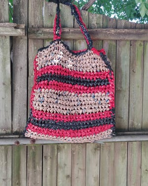 """One of Shari Petrie's favorite creations is her red and black """"project bag."""" She crocehted it using plarn, which is plastic yarn she made from shopping bags."""