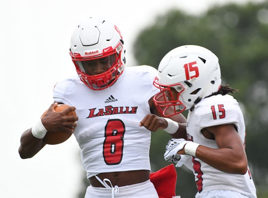 La Salle quarterback MJ Horton (8) and defensive back Devonte Smith (15) bump chests during warm ups against Colerain in the Skyline Chili Crosstown Showdown, Colerain Township, Friday August 24, 2018