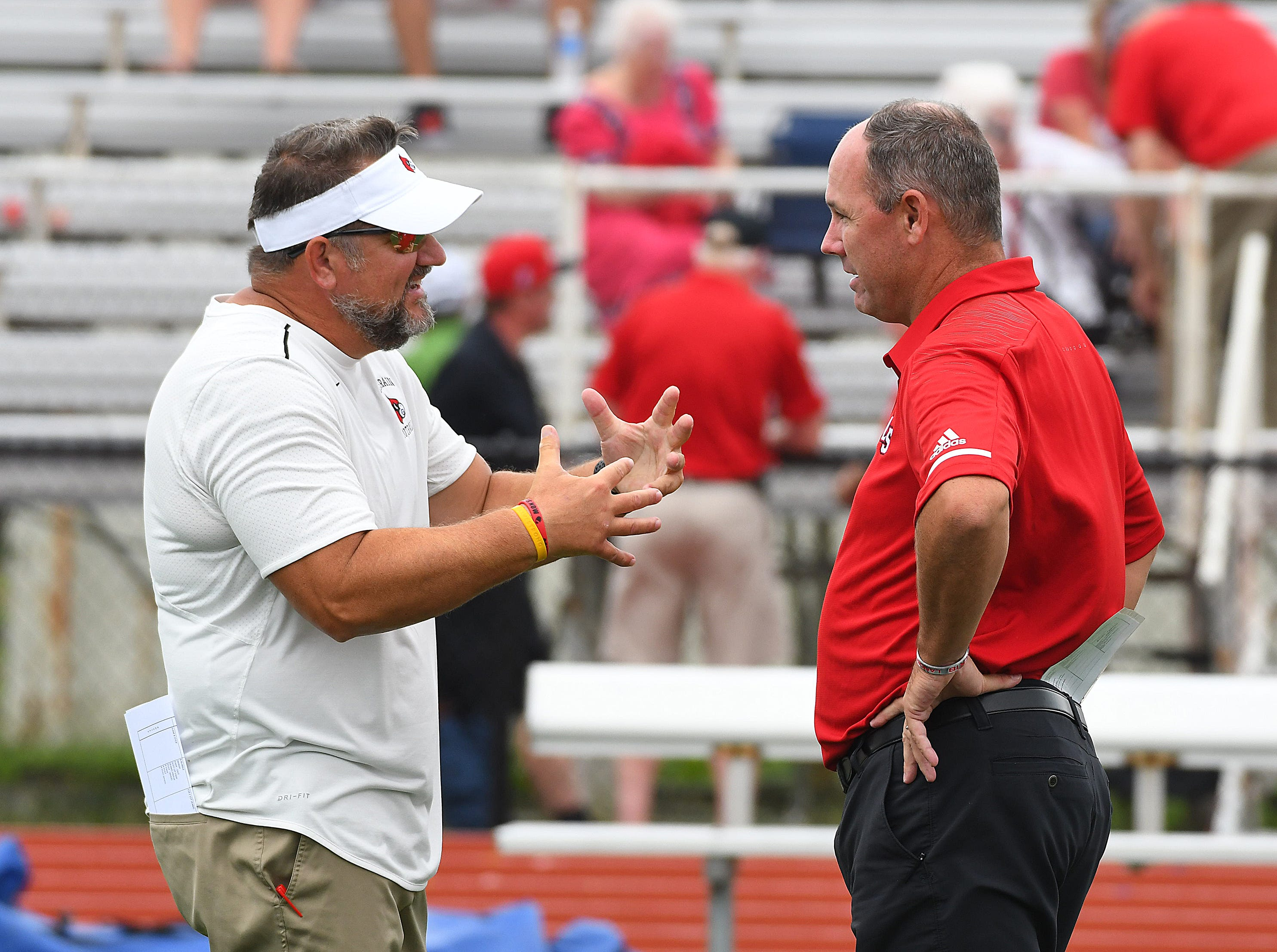 Colerain head coach Tom Bolden (left) talks to LaSalle head coach Pat McLaughlin (right) before the game in the Skyline Chili Crosstown Showdown, Colerain Township, Friday August 24, 2018