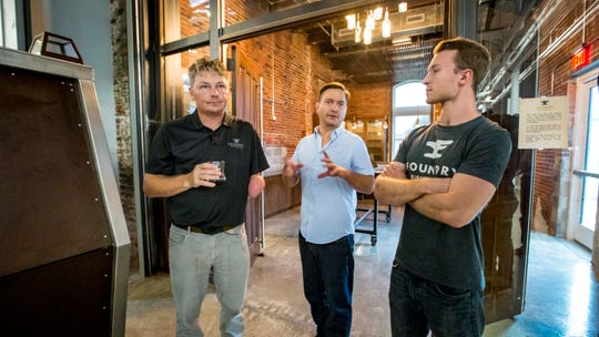 Scott Bush, Founder, Foundry Distilling Co., left, with distillers Cory O'Neel, center, and Greg Biagi, right, during a tour of their new facility and distillery Friday, Aug. 24, 2018, in West Des Moines.