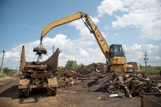 Workers deposit scrap metal into a truck at the Kimmel Scrap Iron & Metal Co. scrap yard in Detroit on Aug. 8, 2018.