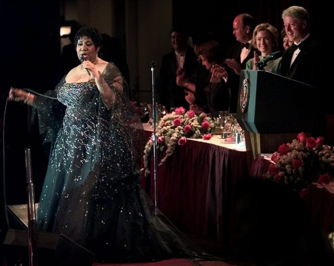 Singer Aretha Franklin, left, gets welcomed on stage by President Clinton and First Lady Hillary Clinton at the White House Correspondents Association dinner at the Washington Hilton in Washington, Saturday, May 1, 1999. Franklin was guest peformer at the event. AWH203