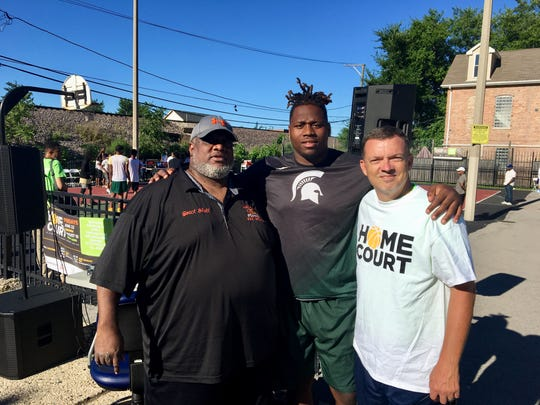 Michigan State defensive tackle Raequan Williams, center, with Garfield Gators youth football director Tim Hall, left, Bill Curry, chief program office of Breakthrough Youth Network.