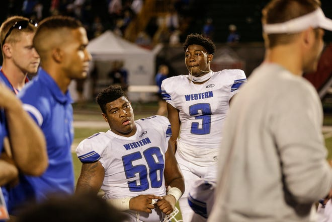 Walled Lake Western's Spencer Brown (58) and CJ Brown (3) after losing to Detroit Catholic Central at a Prep Kickoff Classic game at Wayne State University's Tom Adams Field in Detroit, Thursday, August 23, 2018.