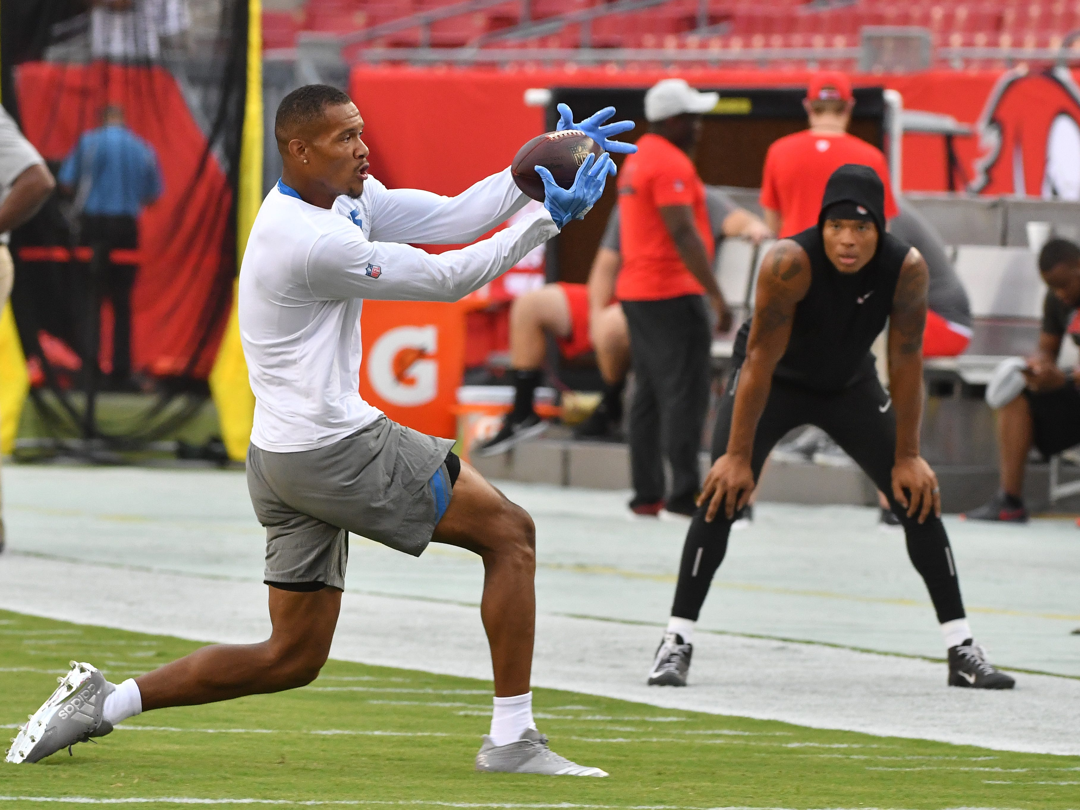 Lions wide receiver Kenny Golladay concentrates on pulling in a reception along the sidelines with teammate Marvin Jones Jr. looking on during warmups.