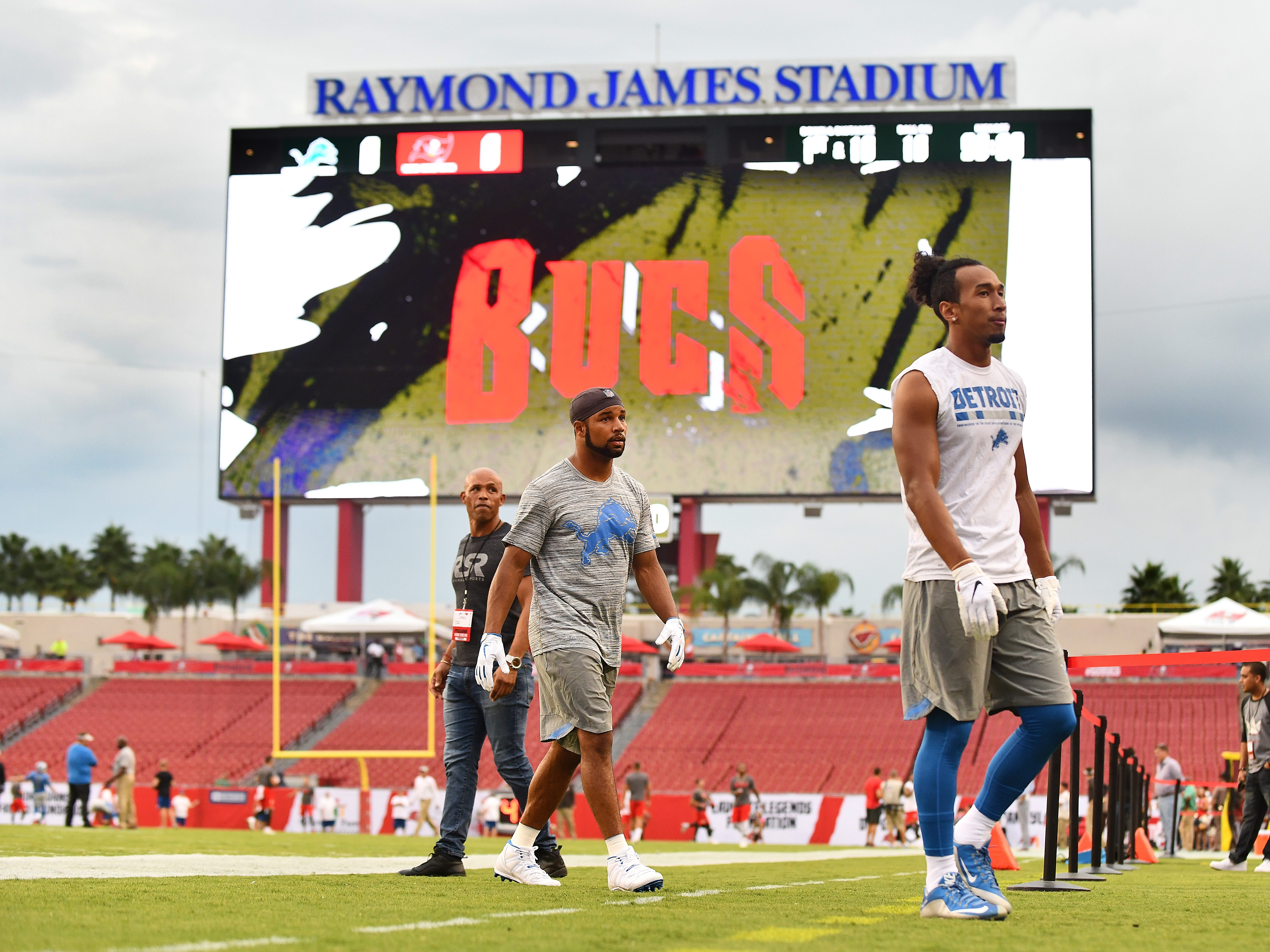 Lions wide receivers Golden Tate and T.J. Jones head off the field during warmups with an ominous sky over head at Raymond James Stadium Friday evening.