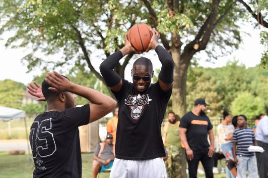 Garlin Gilchrist (right) Democratic Lt. Gov.candidate/running mate for Gretchen Whitmer, makes a play over Jewel Jones, state representative, during the Occupy the Corner event by Detroit Council President Pro Tem Mary Sheffield at Tolan Playfield in Detroit on Friday, August 23, 2018.