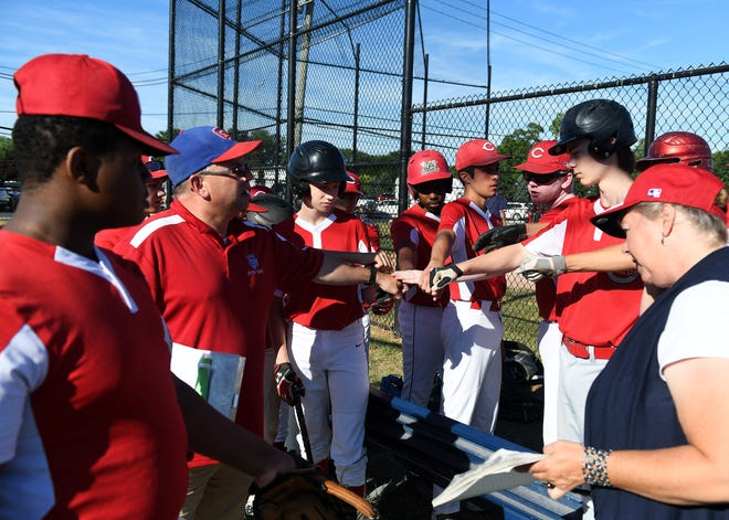 Coach John Huizdos, second from left, fist bumps with the team at the start of the game. Reds vs Pirates in Grosse Pointe Woods-Shores Harper Woods Little League game at Kerby Park Field in Grosse Pointe Farms, Mich. on July 19, 2018.