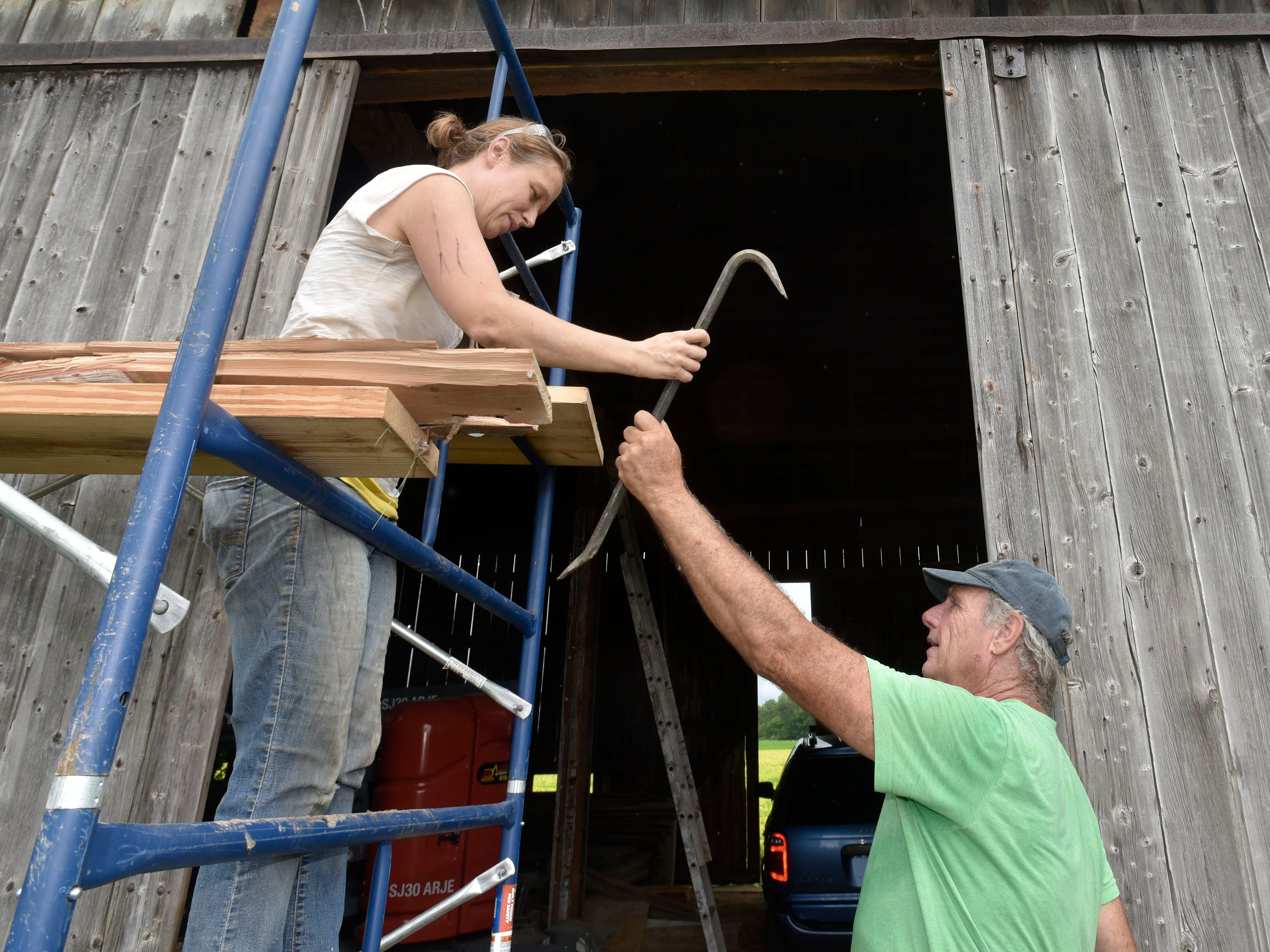 Barn artist Catie Newell of Detroit hands a crowbar to volunteer laborer Terry Boyle, 71, of Port Austin. Boyle, a retired lawyer, now owns and operates six Little Yellow Cottages in Port Austin.