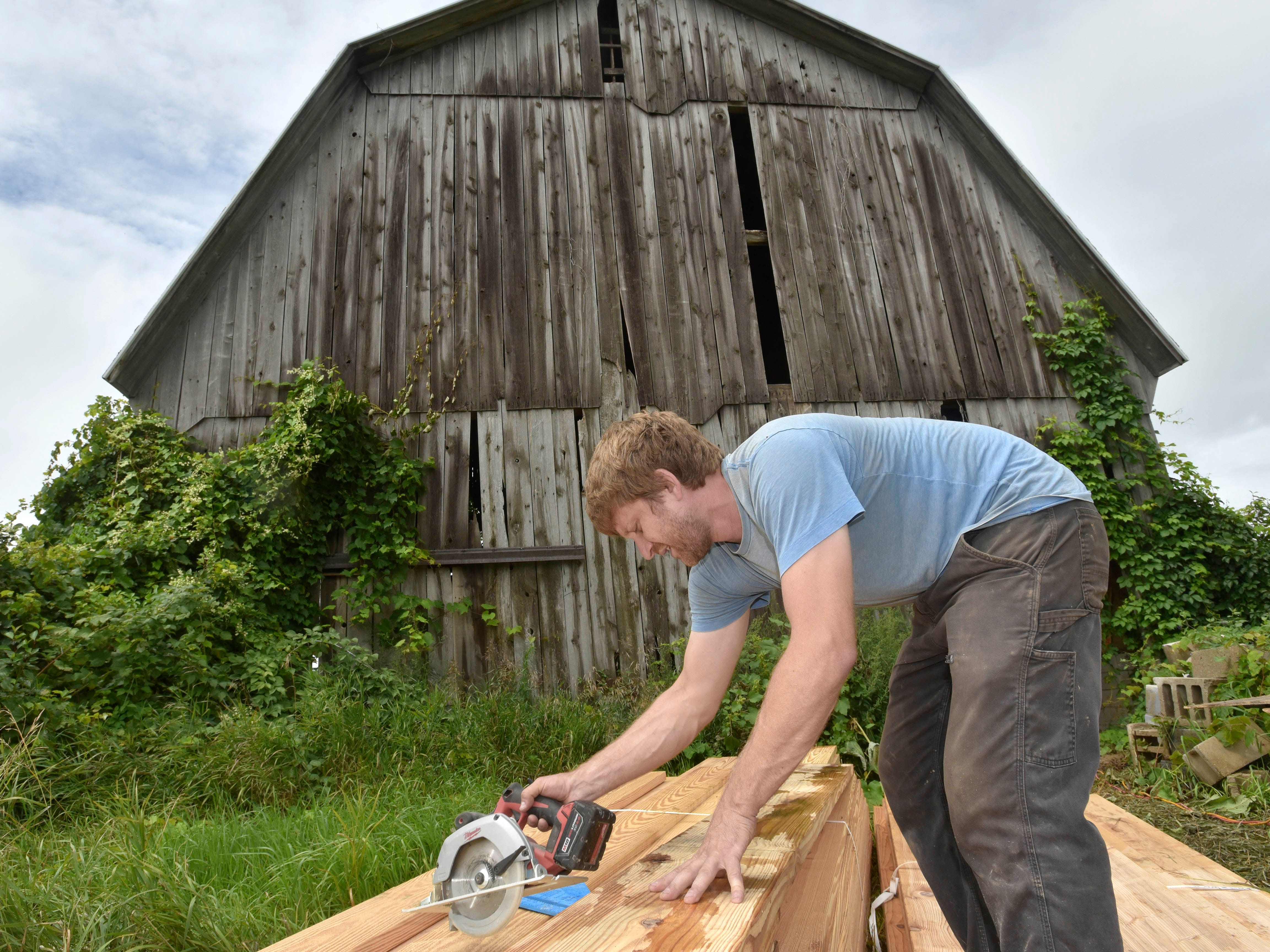 Construction Services owner Charlie O'Geen, 33, of Detroit is a sub-contractor for barn artist Catie Newell, helping her turn this old barn into an art project.