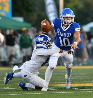 Walled Lake Western's Dawson Cofield, left, starts to tackle Catholic Central quarterback Marco Genrich in the first half during the 2018 Xenith Prep Kickoff Classic at Wayne State University