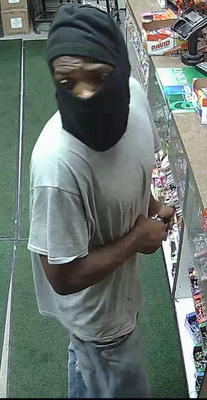 Surveillance cameras captured a man who used two handguns to hold up a gas station customer early Tuesday on the city's west side.