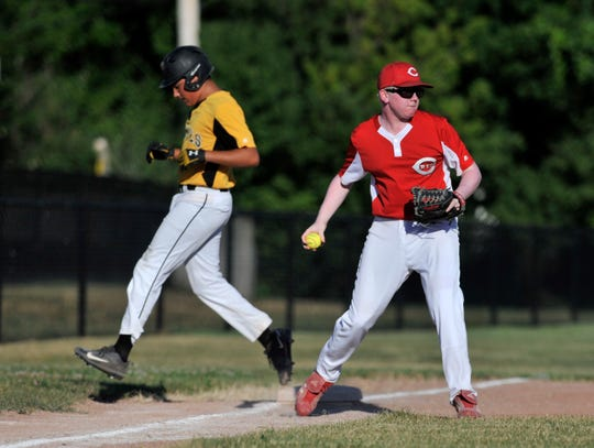 Reds third baseman Ryan Huizdos, right, gets the out at third base while the Reds play the Pirates in a Grosse Pointe Woods-Shores Harper Woods Little League game at Kerby Park Field in Grosse Pointe Farms, Mich. on July 19, 2018. The Reds play with a yellow baseball because one of the players, Ryan Huizdos, has albinism, a visual impairment, and the yellow ball is easier to see.