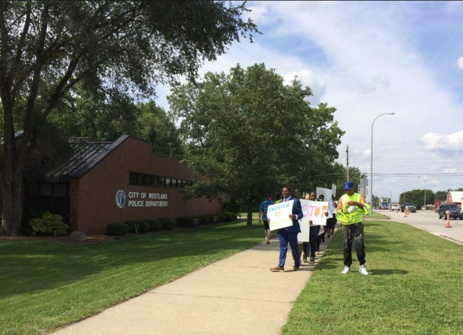 A small group protest the use of a stun gun on a man in front of the Westland Police Department.