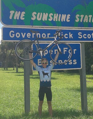 Alex Bennitt of Corning celebrates after riding his bicycle from New York to the Florida state line.