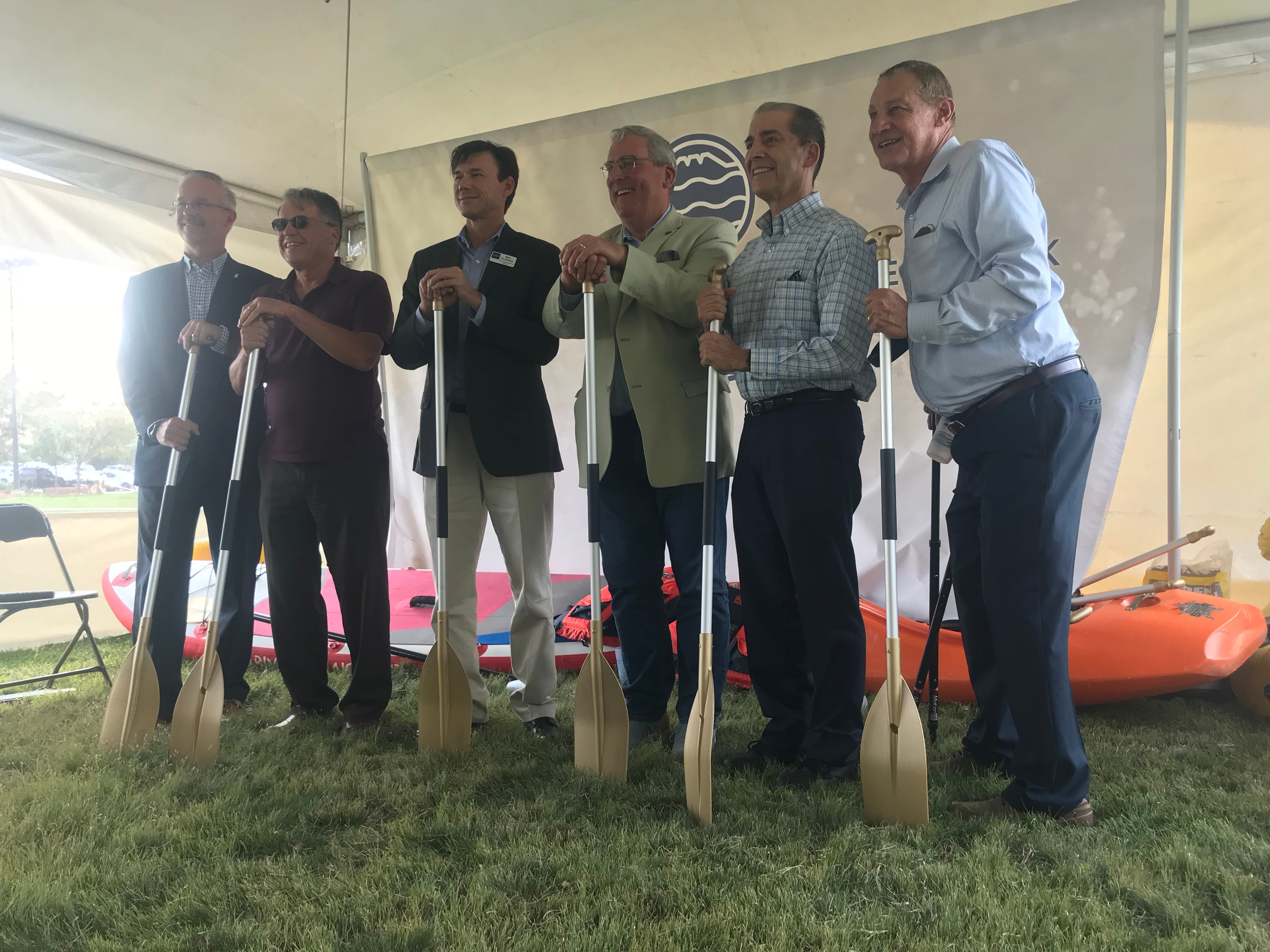"City Manager Darin Atteberry, Mayor Pro Tem Gerry Horak, council member Bob Overbeck, Mayor Wade Troxell and council members Ray Martinez and Ken Summers pose with gold-colored oars at the ""groundbreaking"" of the Poudre River Whitewater Park in Fort Collins on Thursday, Aug. 23, 2018."