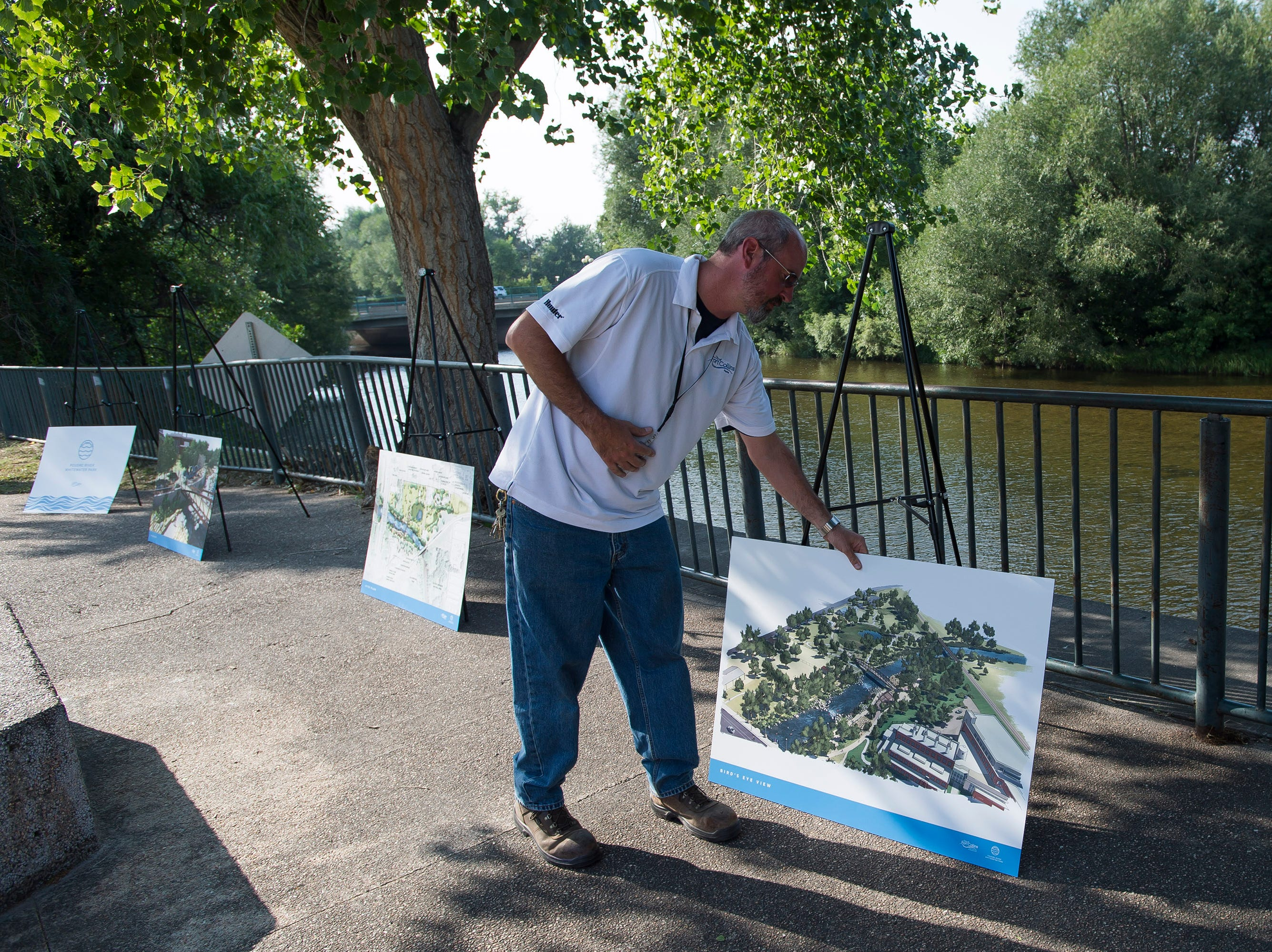 "Fort Collins parks crew chief John Klingamam sets up renderings of the Poudre River Whitewater Park after a ""groundbreaking"" ceremony on Thursday, Aug. 23, 2018, next to the Cache La Poudre River in Fort Collins, Colo."