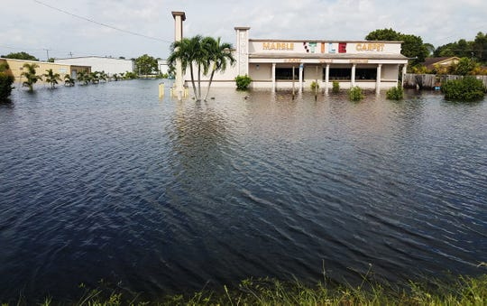 Flood waters encircled PCC Tile on U.S. 41 in the Island Park community of south Fort Myers after record rains fell last August. The store, which was not covered by flood insurance, was closed all of September because of the flooding, said owner Helene Glocer.