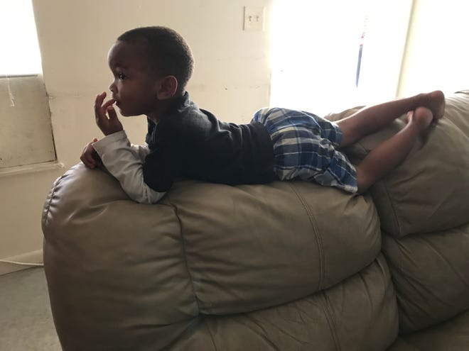 A young boy rest on the back of the couch in one of the apartments. The residents of Jones Walker Complex in Fort Myers is still having trouble getting the much needed maintenance to their apartments. Most feel this place should just be torn down.