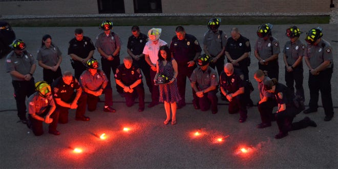 Members of the Oconto Police and Fire Departments surround Amanda Belongia in the final scene of their Lip Sync Challenge video, which was released last week. Amanda is the wife of late OPD officer Erek Belongia. The video, produced to honor Erek, helped members of both departments still grieving over his death two months ago.
