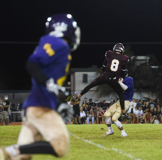 George Washington's Aaron Jamanila makes a catch against Father Duenas Friar Noah Diaz (8) during their Independent Interscholastic Athletic Association of Guam High School Football League game at the George Washington High School football field on Aug. 24, 2018