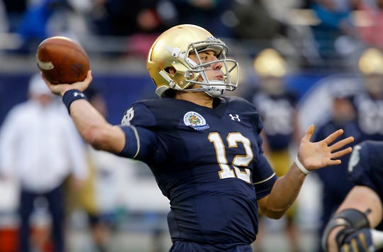 Jan 1, 2018;  Notre Dame Fighting Irish quarterback Ian Book (12) drops to throw a pass during the second half in the 2018 Citrus Bowl at Camping World Stadium.