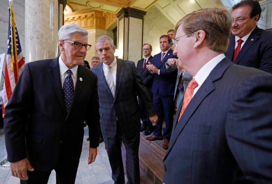 Gov. Phil Bryant, left, House Speaker Philip Gunn, R-Clinton and fellow Republican Lt. Gov. Tate Reeves, confer after a joint news conference explaining the nature of the special session, where they will search for funds to help solve the state's crumbling infrastructure of roads and bridges, Thursday, Aug. 23, 2018 at the Capitol in Jackson, Miss. Republican leaders have outlined a package to divert existing tax revenue, take on debt and create a lottery. (AP Photo/Rogelio V. Solis)